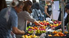 Shoppers explore a local farmers market in Vancouver.