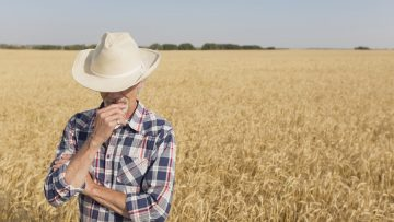 Farmer with head bowed standing in wheat field.