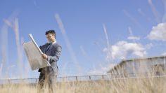 Businessman analyzing blueprint in field