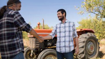 Happy friends shaking hands in farm