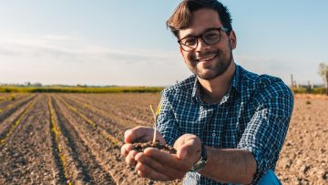 Portrait of farmer standing in field and holding young corn crop with dirt in his hands.